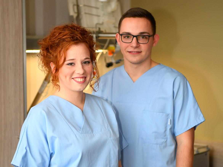 Zwei Auszubildende des Bildungsakademie lächeln in die Kamera.