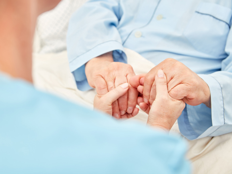 Die Hände einer Pflegerin halten die Hände einer älteren Person.