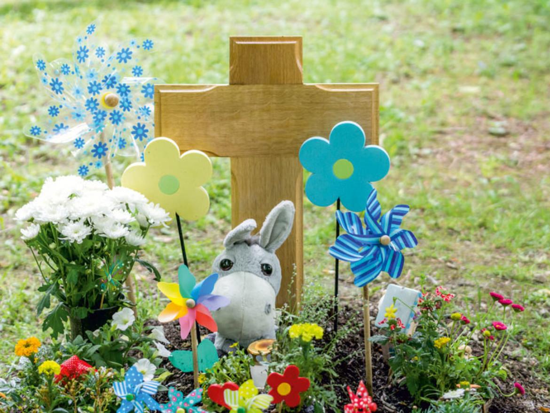 Bild eines bunt geschmückten Kindergrabes. Stofftiere, WIndräder und Blumen sind zu sehen.