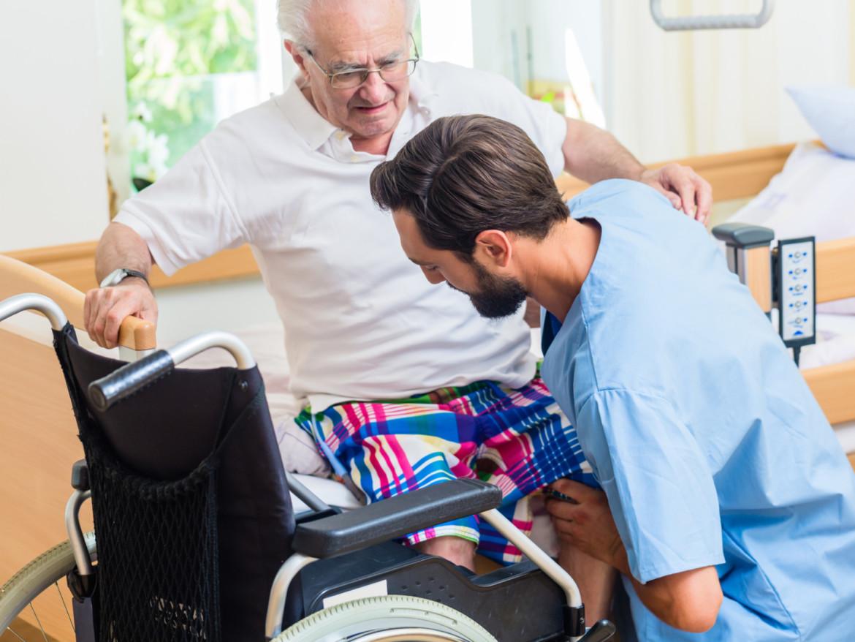 Ein Krankenpfleger hilft einem älteren Patienten vom Bett in den Rollstuhl.