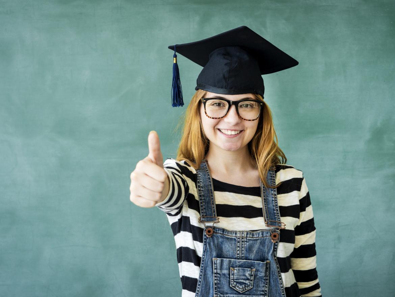Glückliche Studentin reckt den Daumen.