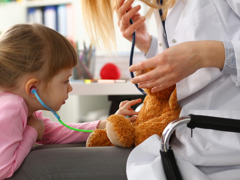 Ein Kleinkind hört einen Teddybären mit einem Stethoskop ab.