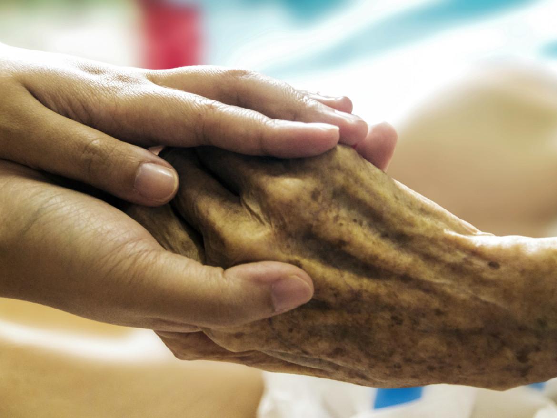 Eine junge Hand streichelt eine alte Hand.