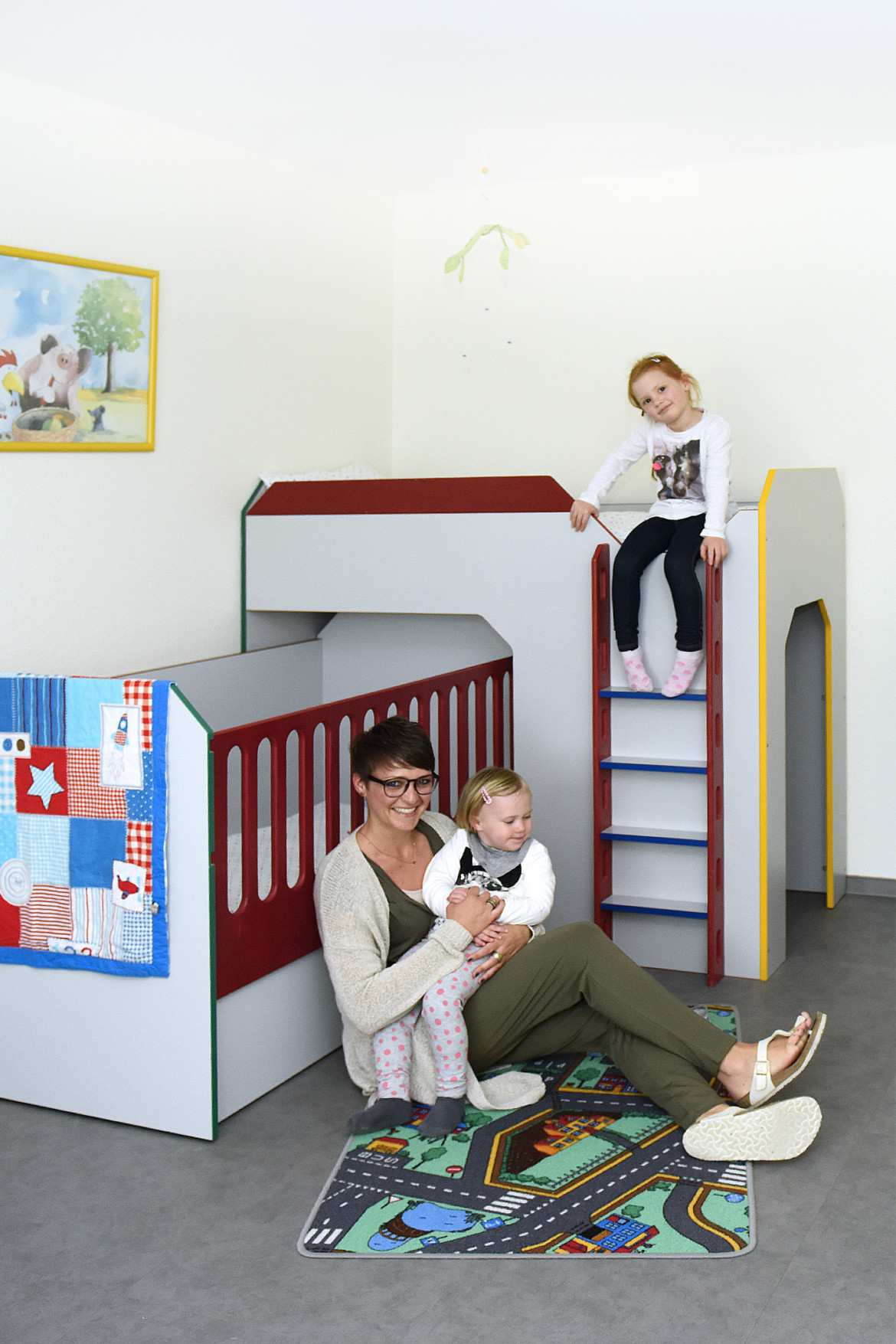 Eine Mutter sitzt mit ihren zwei Kindern in einem freundlich eingerichteten Schlafzimmer des Marianne van den Bosch Hauses.