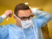 Ein Krankenpflegeschüler legt aus hygienischen Gründen einen Mundschutz an.