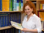 Eine Krankenpflegeschülerin steht lächelnd in der Bibliothek der Bildungsakademie.