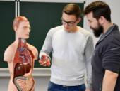 Ein Krankenpflegeschüler betrachtet das Modell eines menschlichen Körpers samt Organen.