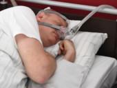 Ein Patient mit Sauerstoffmaske schläft im Schlaflabor.