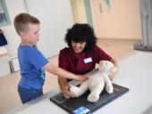 Eine Mitarbeiterin des St.-Antonius-Hospitals erläutert einem kleinen Jungen und seinem Teddy das Röntgen.
