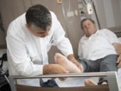 Chefarzt Dr. Gündug untersucht den Fuß eines Diabetes-Patienten.