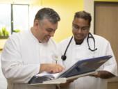 Chefarzt Dr. Gündug erläutert einem Kollegen die Akte eines Patienten.