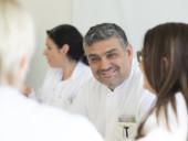 Chefarzt Dr. Gündug lächelnd im Kreis seines Teams.