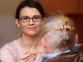 Eine Junge Altenpflegerin blickt an einer Senioren vorbei freundlich in die Kamera.