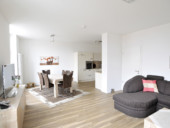 Blick in den hellen und geräumigen Wohn- und Essbereich einer seniorengerechten Wohnung.
