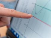 Ein Fingerzeig auf den Monitor eines Computers, im Bild eine Verlaufskurve.