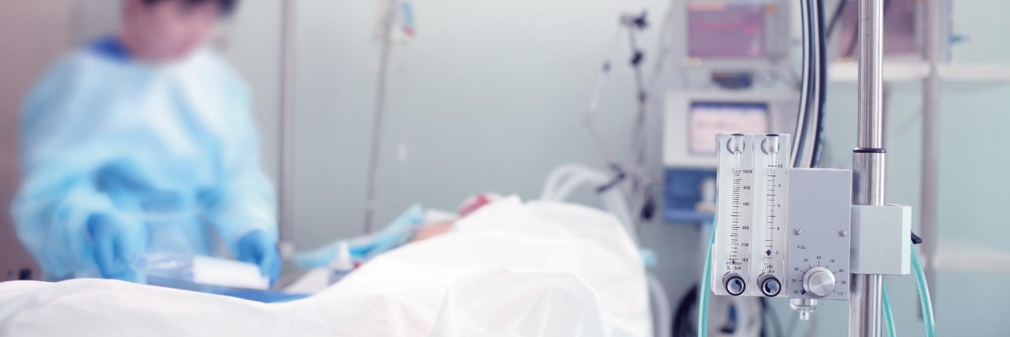 Eine Pflegekraft steht am Bett eines Patienten auf der Intensivstation.