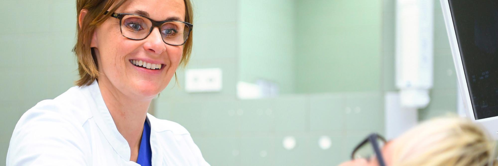 Oberärztin Stefanie Untiedt bei der Untersuchung einer liegenden Patientin.