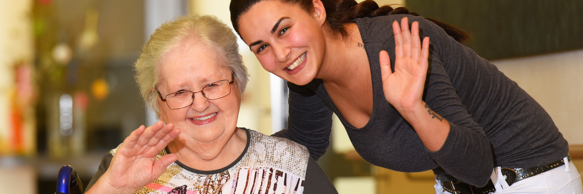 Eine Seniorin und eine Altenpflegerin winken gemeinsam in die Kamera.