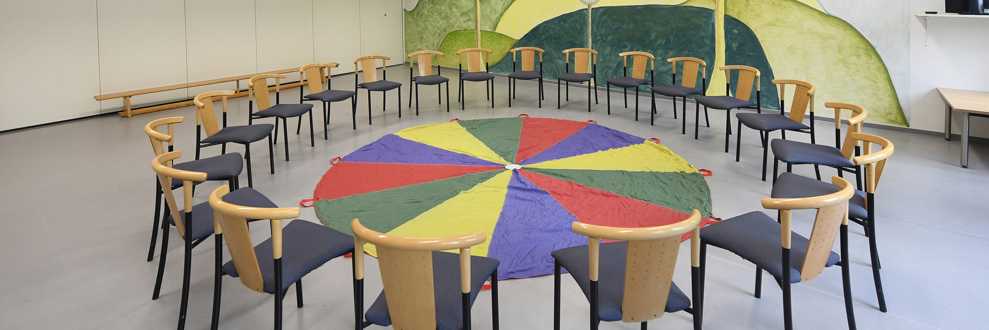 Ein großer Stuhlkreis umschließt ein Schwungtuch im großzügigen Therapieraum des Marianne van den Bosch Hauses.