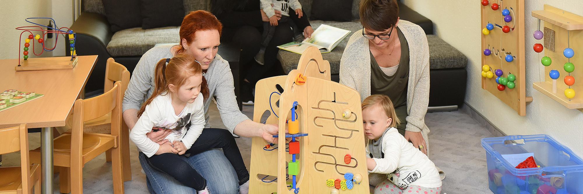 Drei Mütter und Ihre Kinder spielen gemeinsam in einem Aufenthaltsraum des Marianne van den Bosch Hauses.