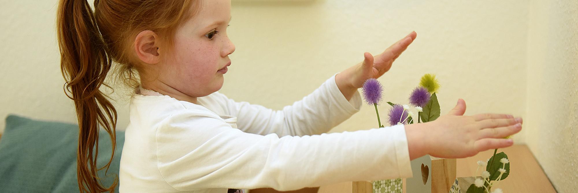 Ein Kind spielt mit Holzblumenvasen im Marianne van den Bosch Haus.
