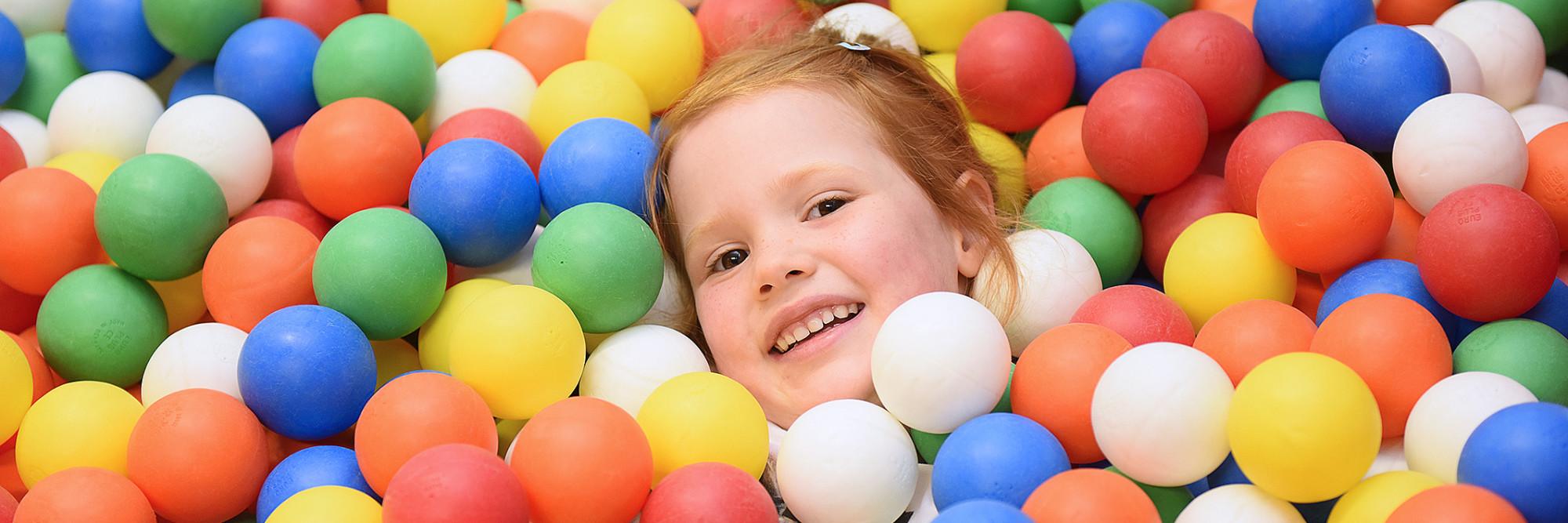 Ein Kind schaut glücklich aus einem Bällebad.
