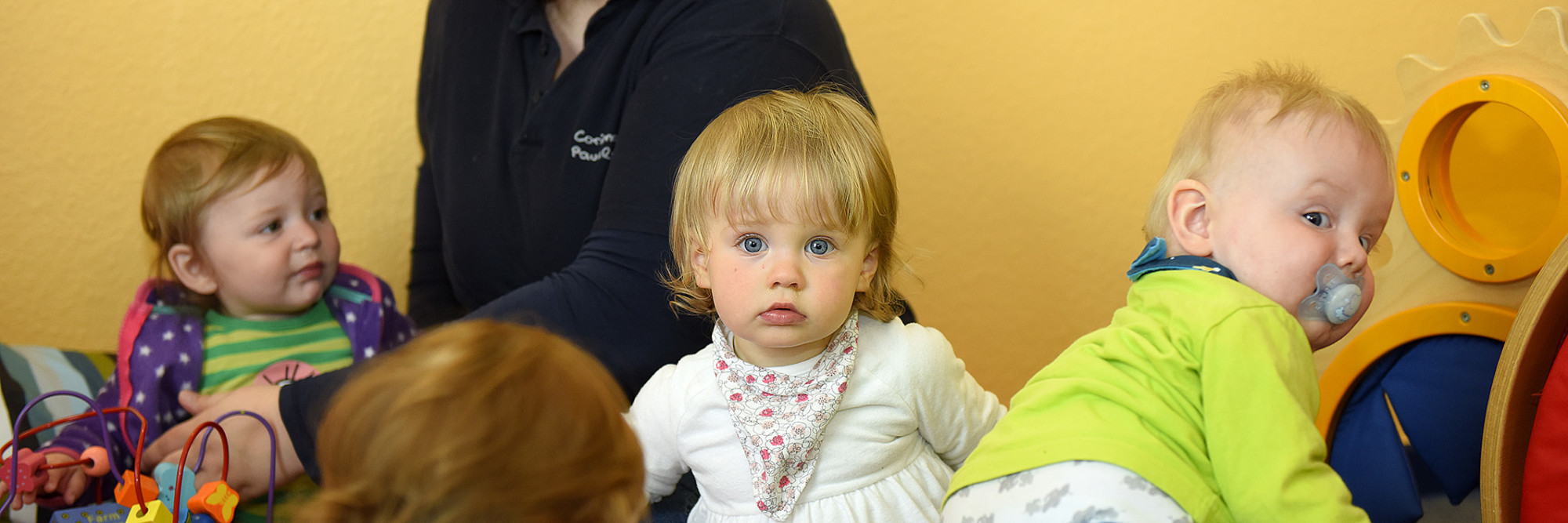 Eine Erzieherin kümmert sich im Kinderland des Marianne van den Bosch Hauses um eine Gruppe Kleinkinder.
