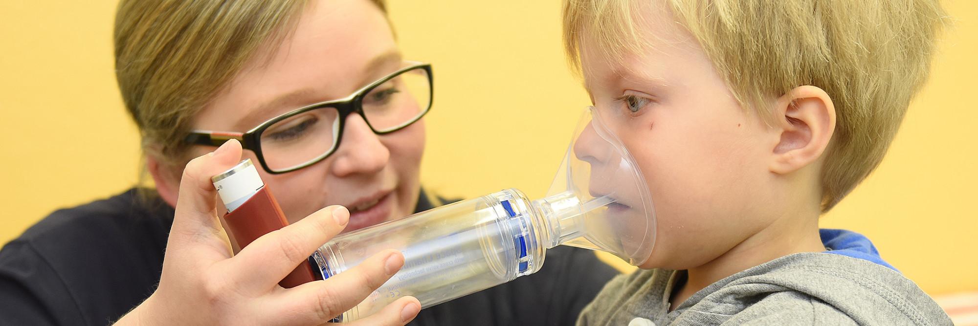 Ein Kleinkind inhaliert mit Hilfe einer Erzieherin im Kinderland des Marianne van den Bosch Hauses.