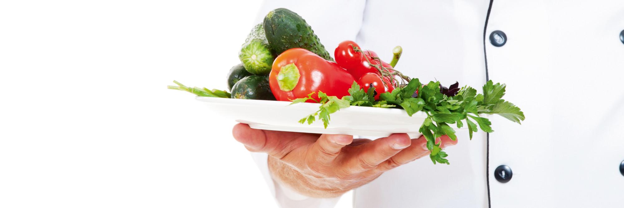 Ein Koch - nicht erkennbar - präsentiert einen Teller frischer Gemüse.