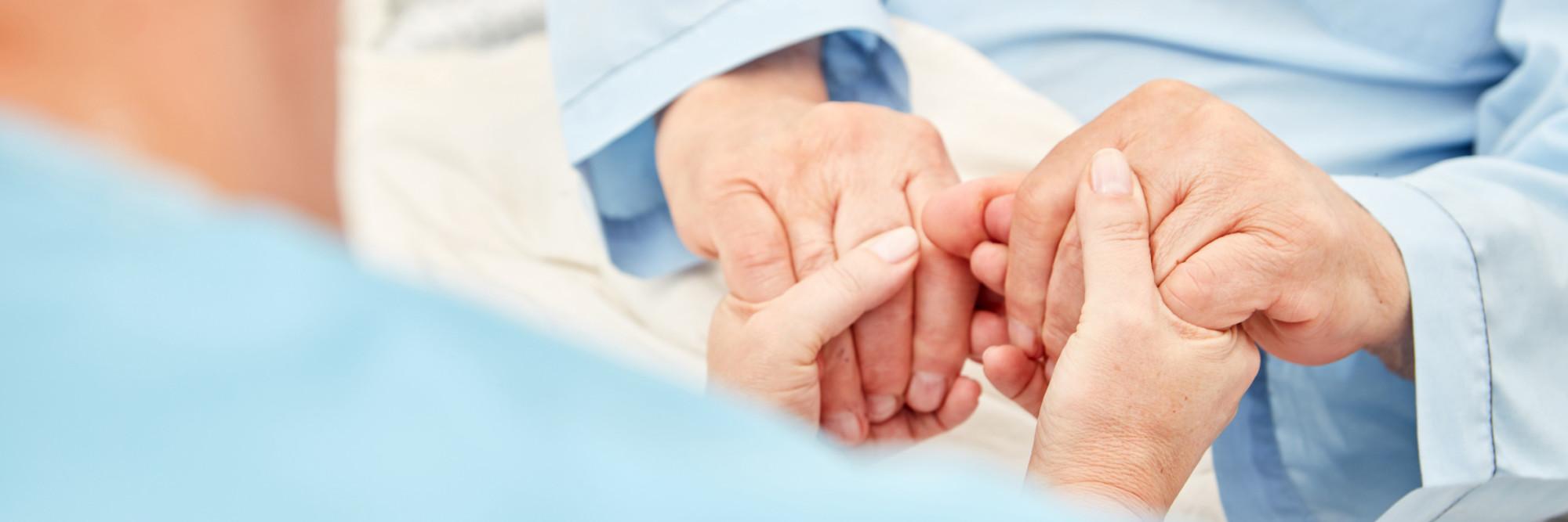 Zwei Hände halten zwei andere Hände und vermitteln Zugewandtheit.
