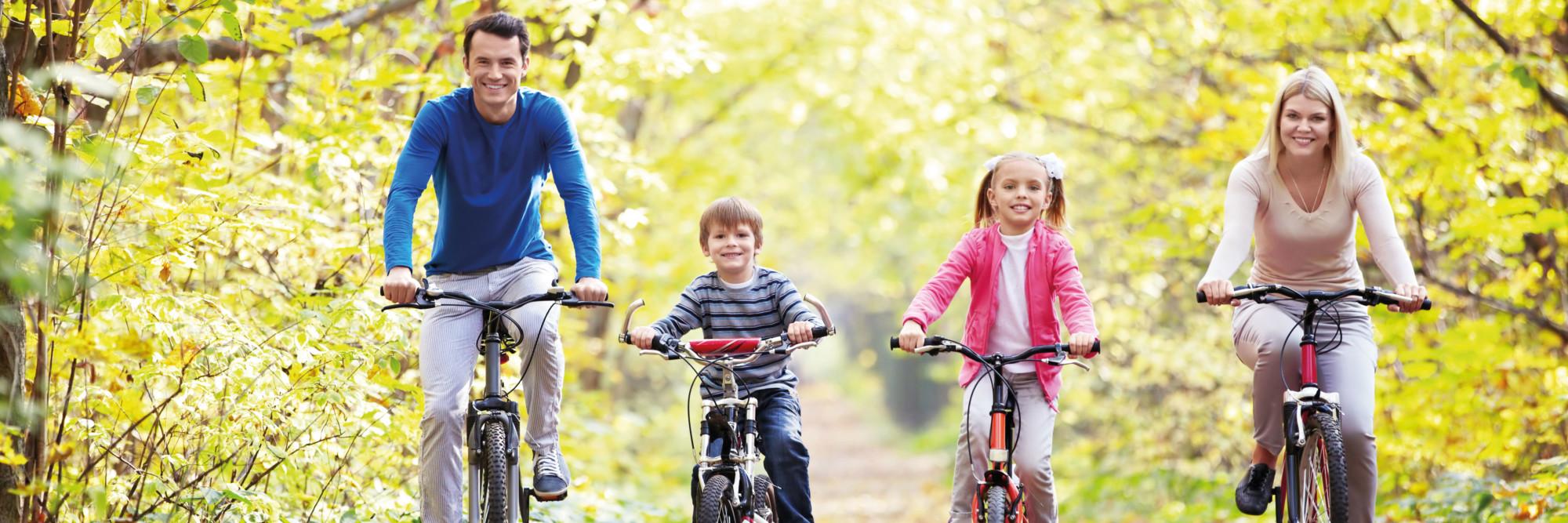 Eine glückliche junge Familie mit zwei Kindern fährt Fahrrad durch den Wald.