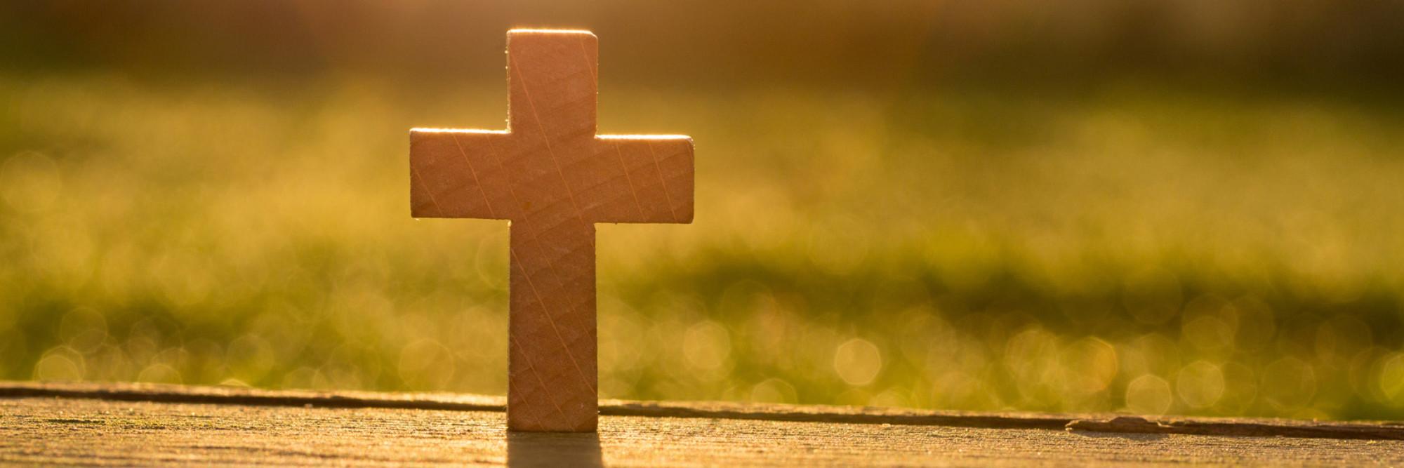 Ein Holzkreuz steht auf einem Holztisch. Der Blick schweift ins Gegenlicht, ins Freie.