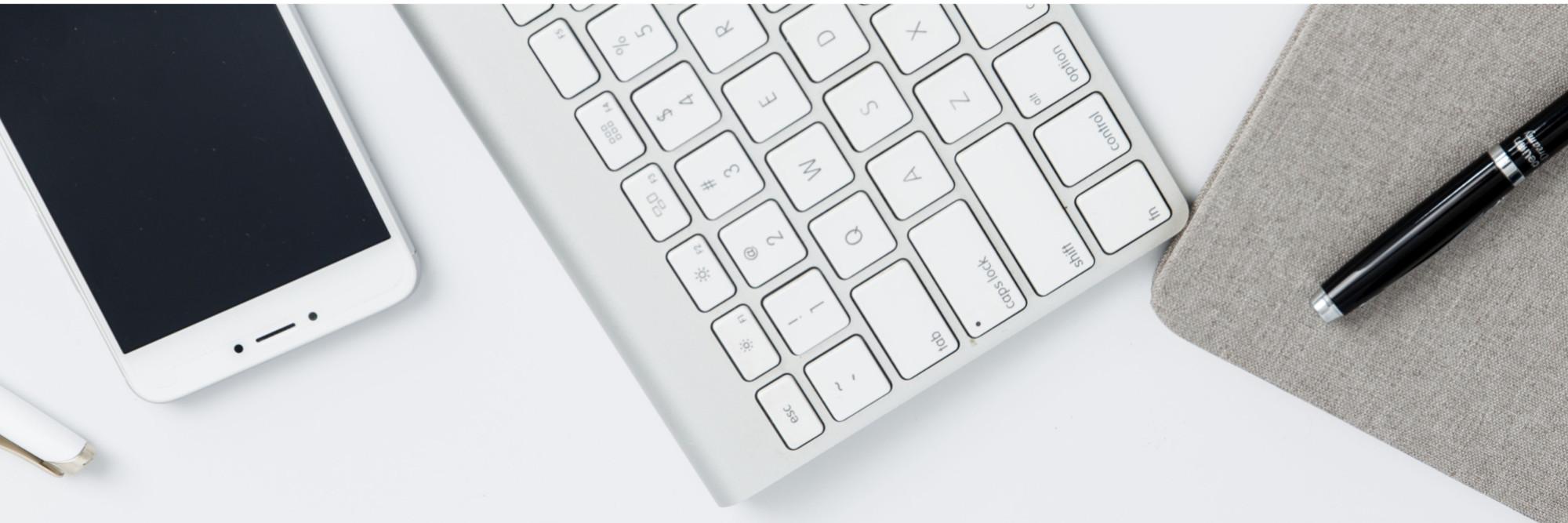 Blick auf einen Schreibtisch: Tastatur, Handy und Stift.
