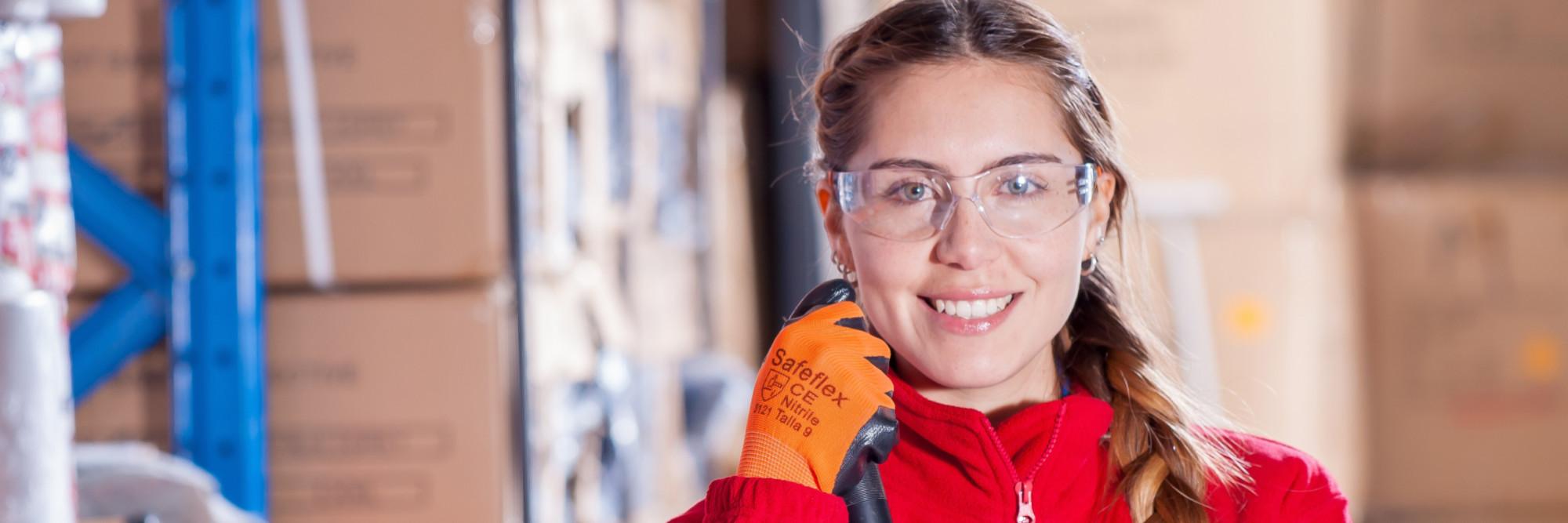 Eine junge Lagerarbeiterin mit Schutzbrille und Handschuhen blickt in die Kamera.