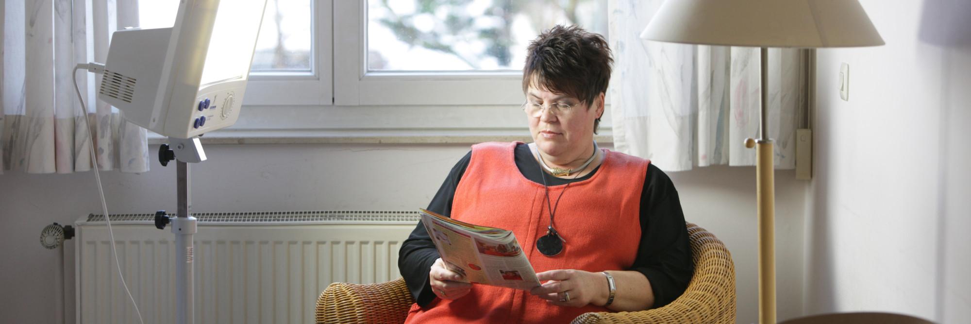 Eine Patienten des St. Nikolaus-Hospitals liest während der Lichttherapie in einem Magazin.