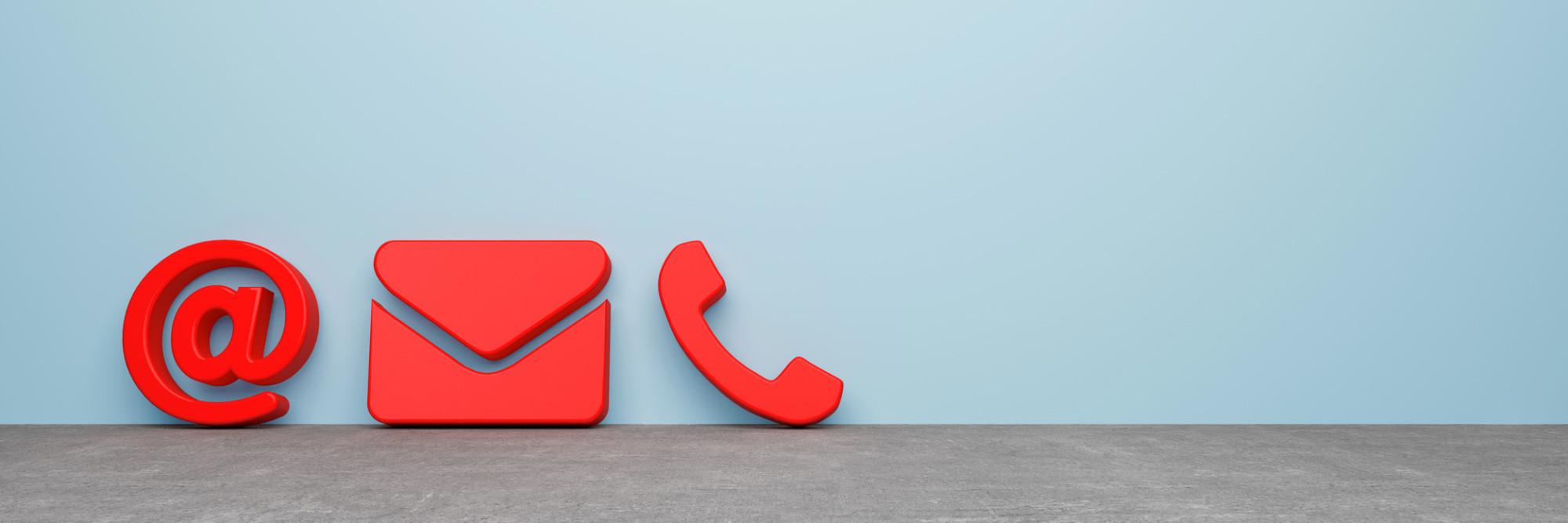 @-Zeichen, Mail-Zeichen und Telefonhörer lehnen als rote Symbole vor einer grauen Wand.