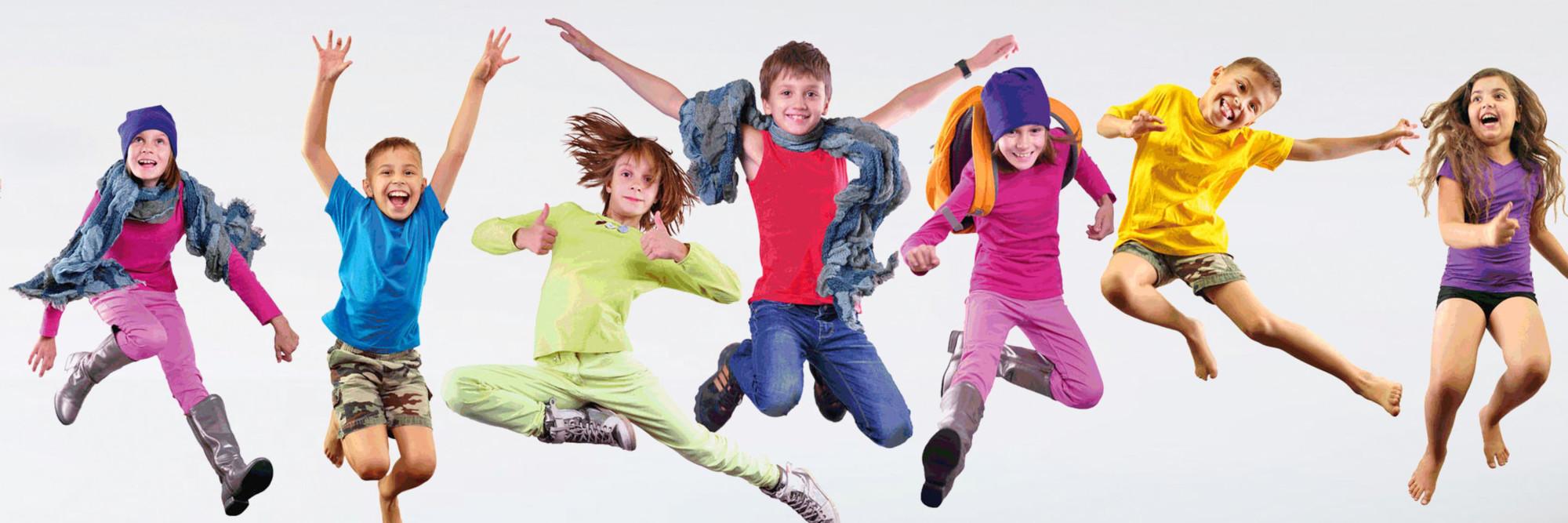 Sieben Kinder - bunt gekleidet - springen lebenslustig in die Höhe.