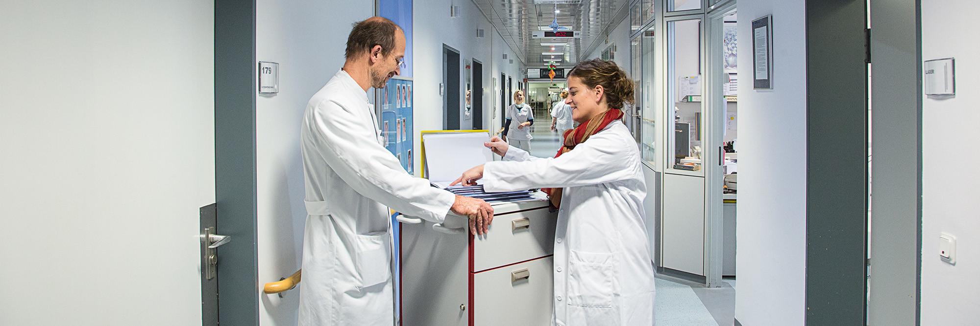 Eine Apothekerin berät einen Arzt zur Medikation, im Hintergrund ein hell erleuchteter Krankenhausflur.
