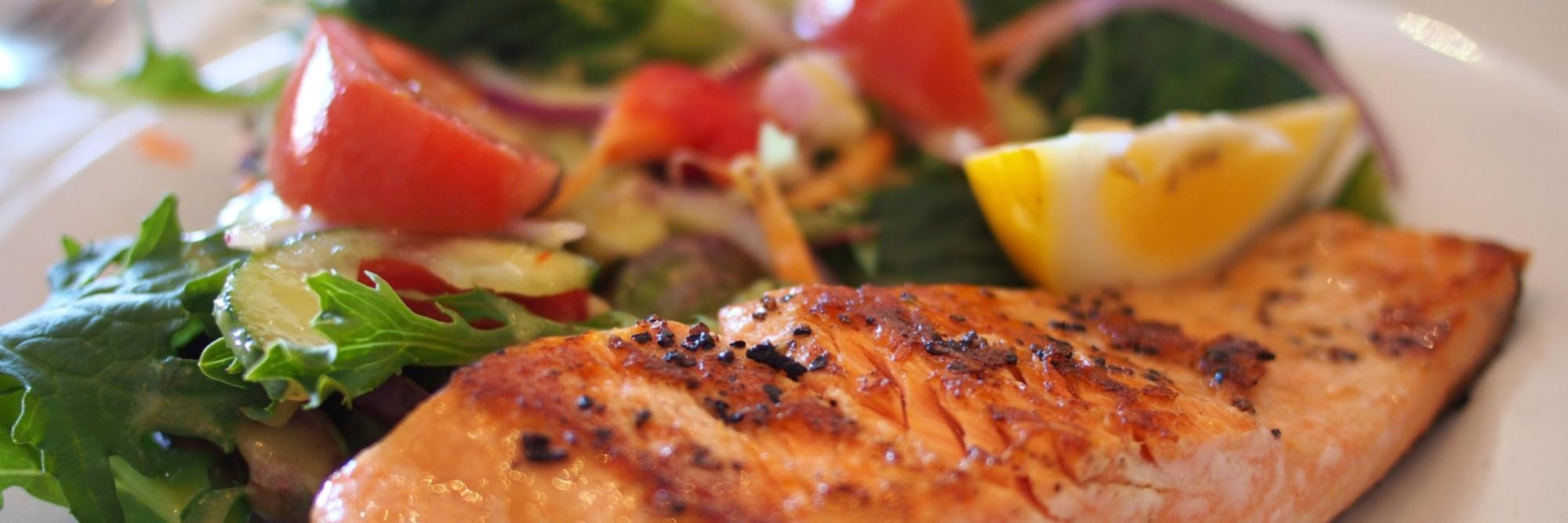 Detailfoto eines schmackhaften Mittagsmenüs - gebratenes Lachsfilet mit einem frischen Salat.