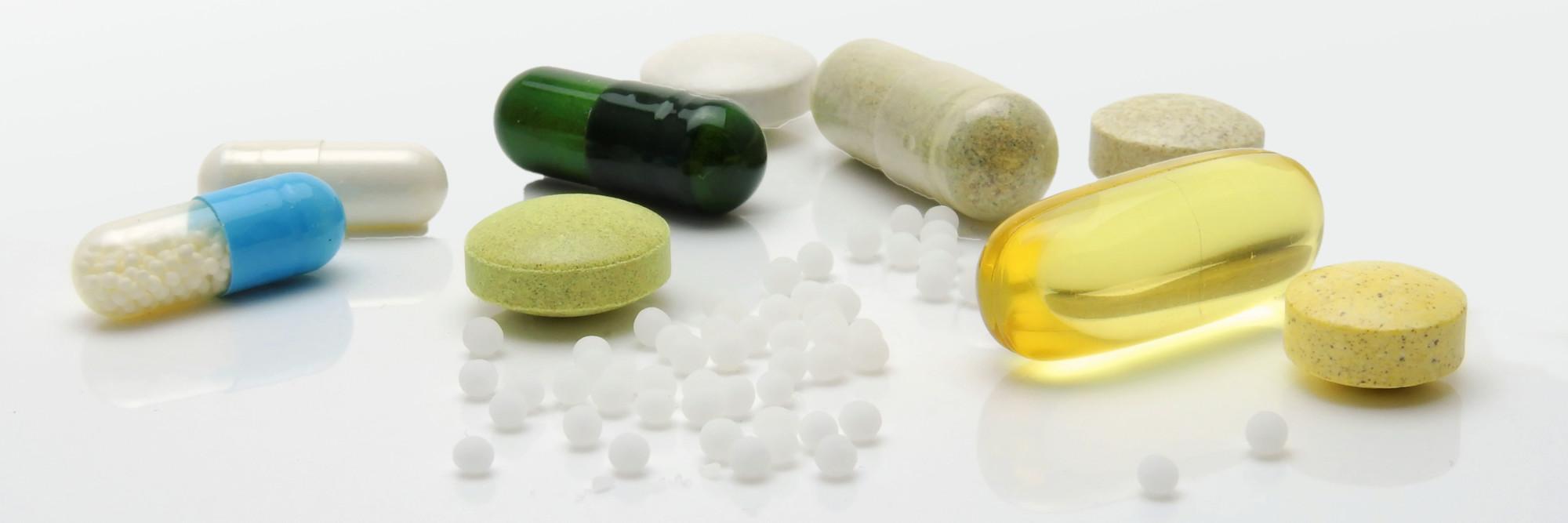 Verschiedene Tabletten liegen auf einer glänzenden Fläche.