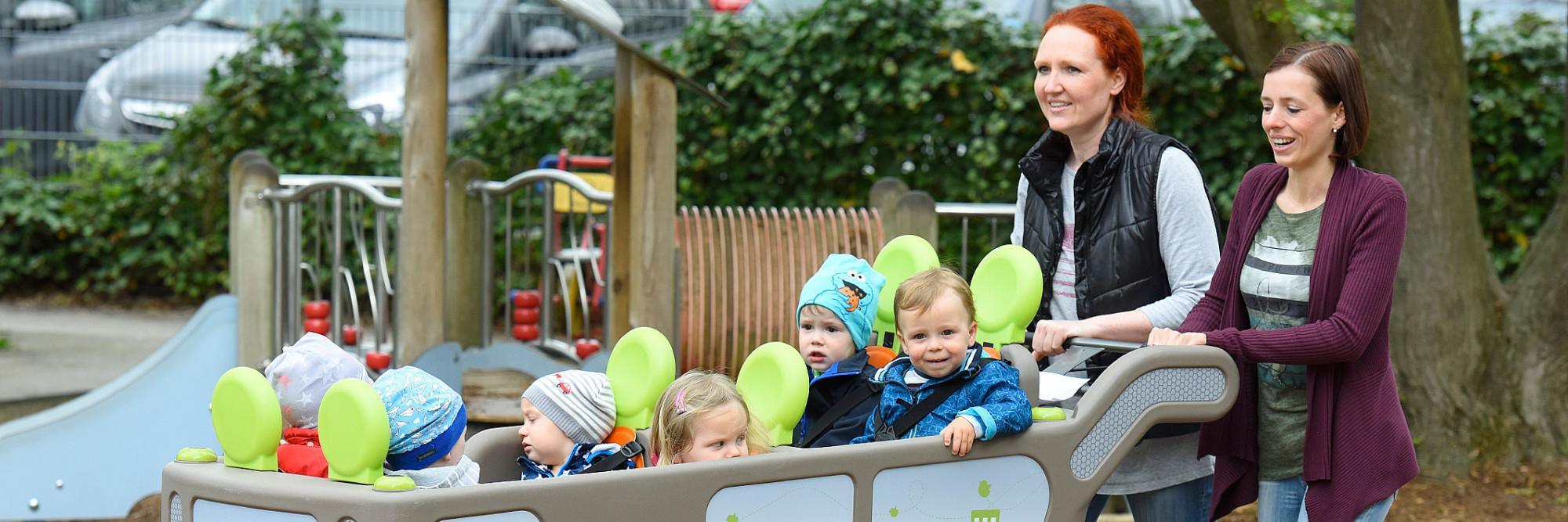Zwei Mütter schieben fünf Kinder in einem großen Kinderwagen.
