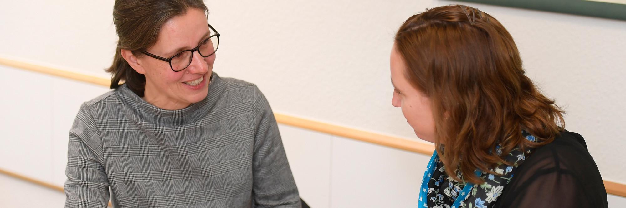 Eine Mitarbeiterin des Marianne van den Bosch Hauses im Gespräch mit einer Mutter.