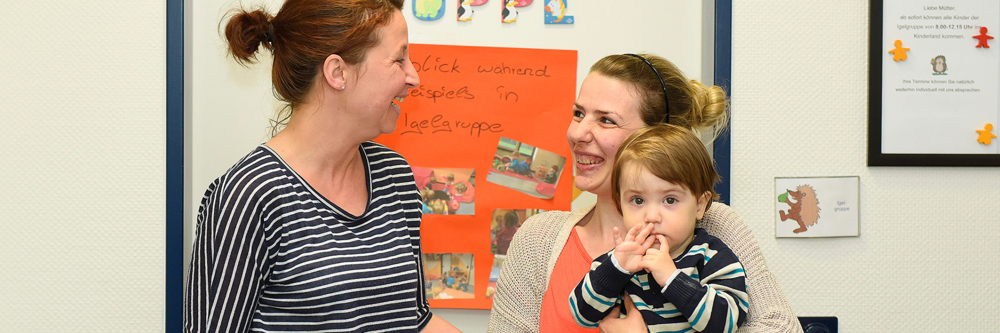 Eine Mitarbeiterin des Marianne van den Bisch Hauses im Gespräch mit einer Mutter und ihrem Kind.