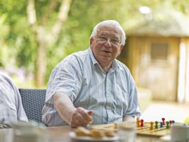 Ein Gast der Tagespflege sitzt zufrieden am Tisch, vor ihm ein Mensch-Ärgere-Dich-Nicht-Spiel.