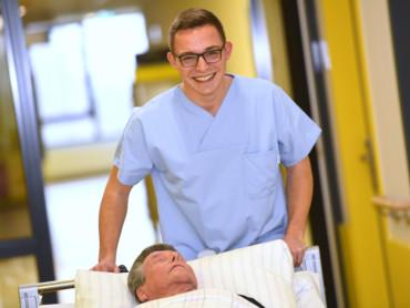 Ein Krankenpflegeschüler schiebt lächelnd ein Bett über einen Krankenhausflur.