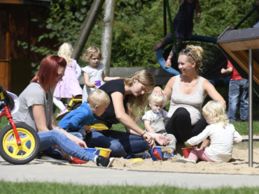 Mütter spielen mit ihren Kindern auf dem großzügigen Außengelände des Marianne van den Bosch Hauses.