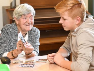 Eine Seniorin zeigt einem Jugendlichen Fotos aus ihrer Kindheit - beide lächeln.