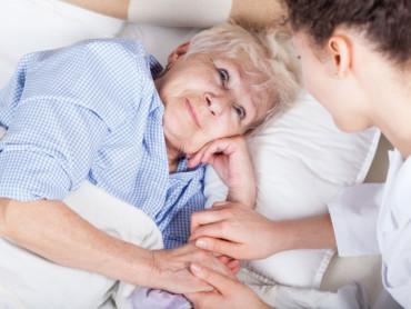Eine Pflegerin hält eine ältere Patientin bei den Händen.