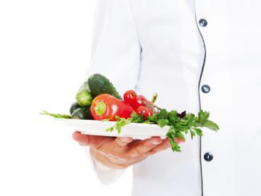Ein Koch reicht einen appetitlichen Teller mit frischem Gemüse.