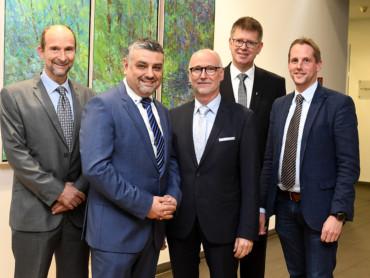 Geschäftsführer Bernd Ebbers begrüßt Dr. Ufuk Gündug per Handschlag. Mit im Bild: Professor Volker Runde, Propst Johannes Mecking und Holger Hagemann.